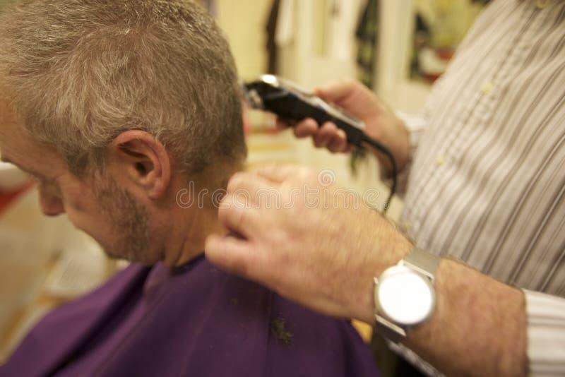 Midsection daje ostrzyżeniu klient w salonie starszy fryzjer męski obrazy royalty free