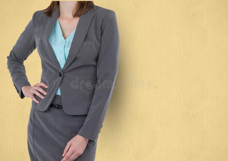 Midsection de la empresaria que se opone con la mano en cadera a fondo amarillo foto de archivo