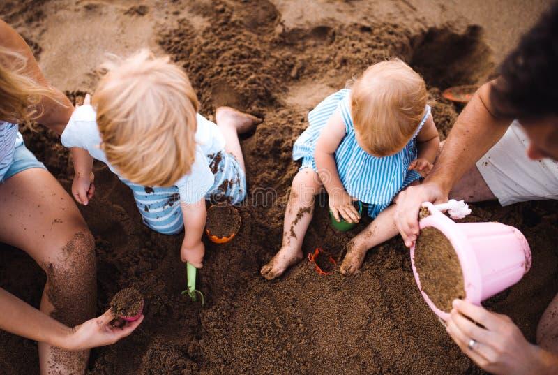 Midsection de la familia con los niños del niño que juegan en la playa el vacaciones de verano foto de archivo libre de regalías