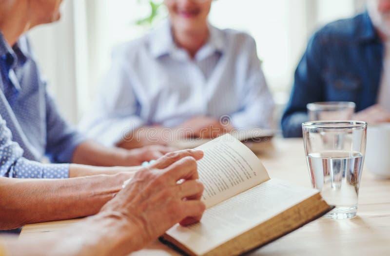 Midsection de la gente mayor en grupo de la lectura de la biblia en club del centro de la comunidad foto de archivo libre de regalías