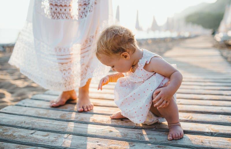 Midsection de la madre joven con una niña pequeña en la playa el vacaciones de verano imagenes de archivo
