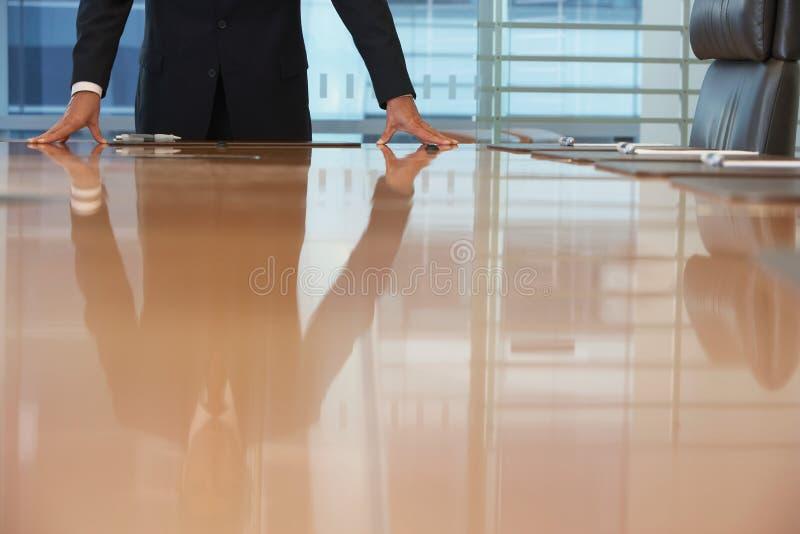 Midsection de la mesa de reuniones de With Hands On del hombre de negocios imágenes de archivo libres de regalías
