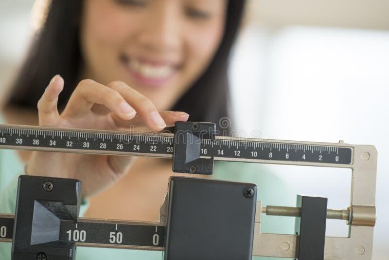 Midsection de la mujer que sonríe mientras que ajusta la escala del peso imagen de archivo