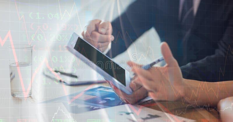 Midsection de los hombres de negocios con la tableta que discuten en oficina imagen de archivo
