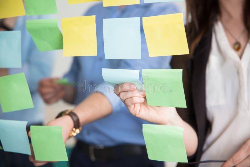 Midsection de los hombres de negocios que pegan notas adhesivas en el vidrio imagen de archivo libre de regalías