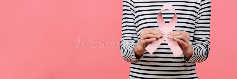 Midsection de una mujer joven que sostiene la cinta rosada de la conciencia del cáncer de pecho aislada sobre fondo coralino de v imágenes de archivo libres de regalías