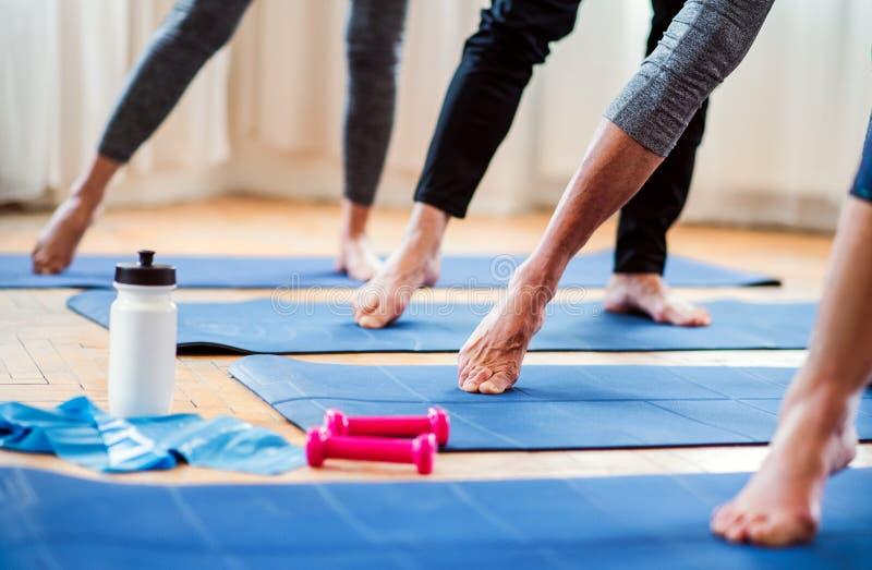 Midsection del grupo de gente mayor que hace ejercicio en club del centro de la comunidad imagen de archivo