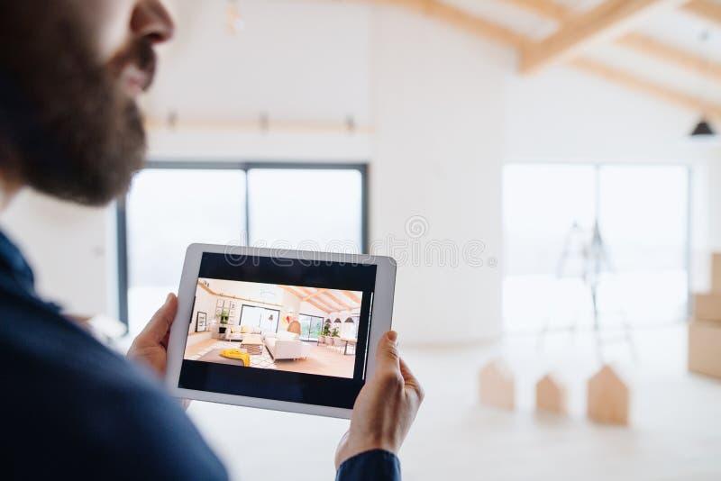 Midsection del hombre con la tableta, mirando bosquejos del diseño interior Un nuevo concepto casero foto de archivo libre de regalías