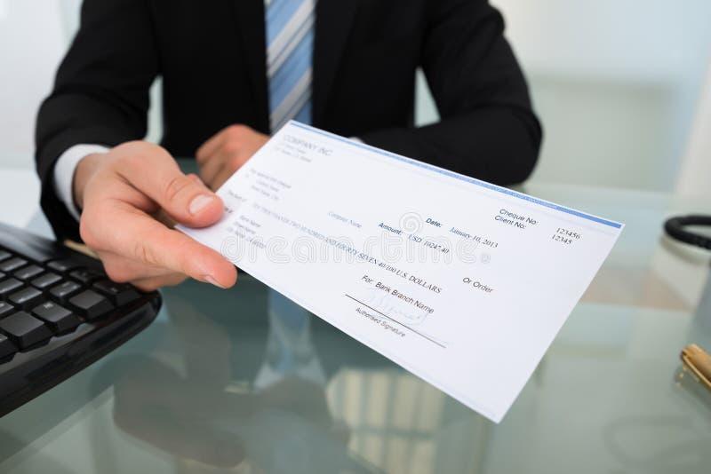Midsection del hombre de negocios que da el cheque fotografía de archivo