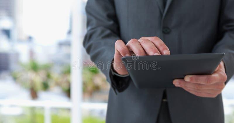 Midsection del hombre de negocios usando la tableta imagen de archivo libre de regalías