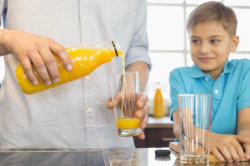 Midsection del padre que sirve el zumo de naranja para el hijo en cocina imagenes de archivo