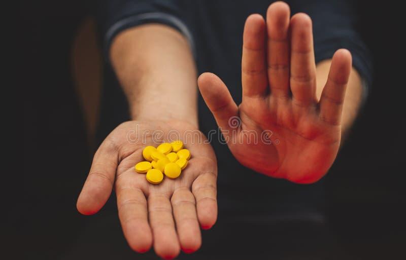 Midsection del primo piano dell'uomo che tiene le pillole delle medicine con il gesto di arresto contro il fondo nero immagini stock libere da diritti