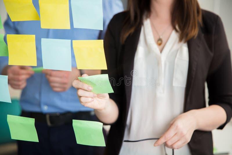 Midsection del vidrio de Sticking Note On de la empresaria por el ejecutivo imagen de archivo