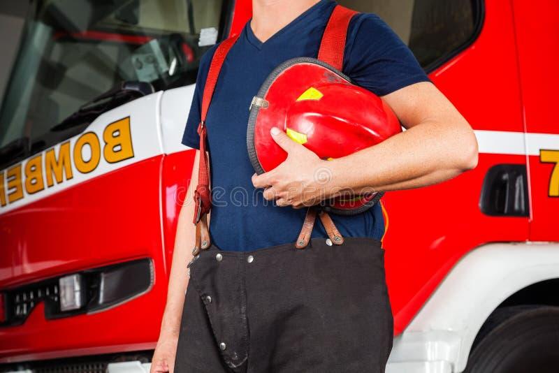 Midsection del vigile del fuoco che tiene casco rosso immagini stock