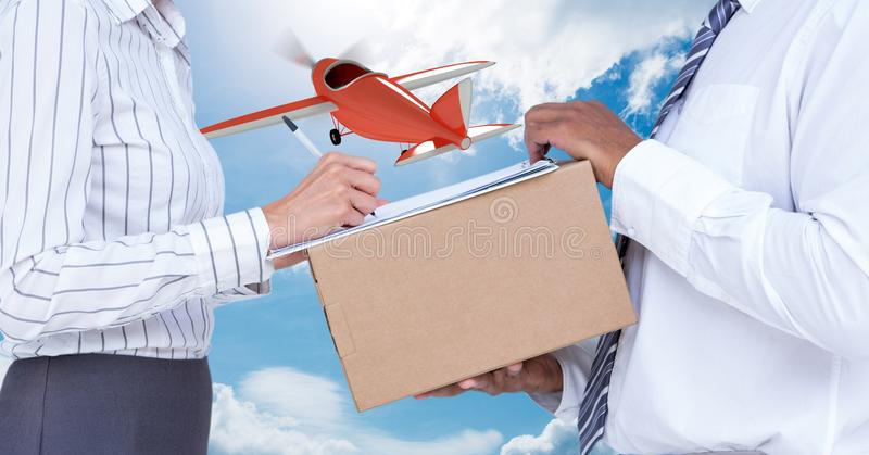 Midsection of delivery man taking sign of woman while delivering parcel with airplane in background royalty free stock photos