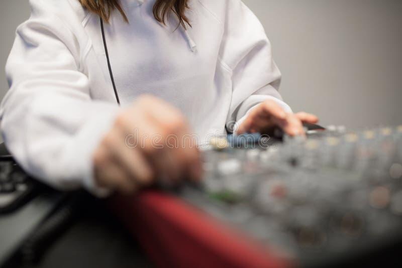 Midsection dell'ospite radiofonico facendo uso del miscelatore di musica in studio immagine stock libera da diritti
