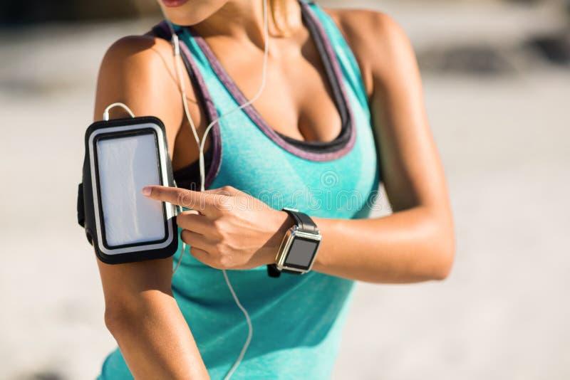 Midsection della donna che per mezzo dello smartphone sul bracciale immagini stock
