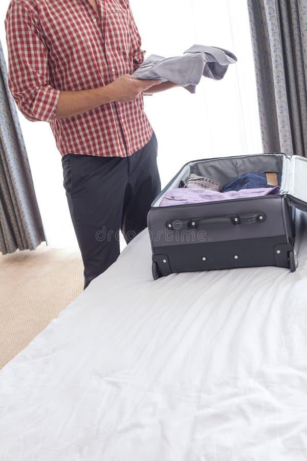 Midsection die van jonge zakenman overhemd van koffer in hotelruimte nemen stock afbeeldingen