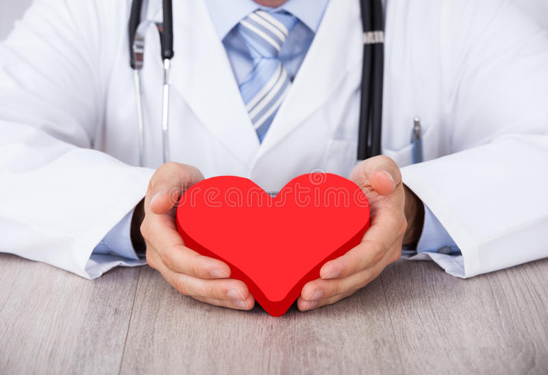 Midsection of doctor holding red heart at desk stock photos