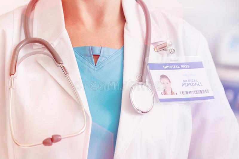 Midsection of doctor with stethoscope and identity card at hospital stock photo