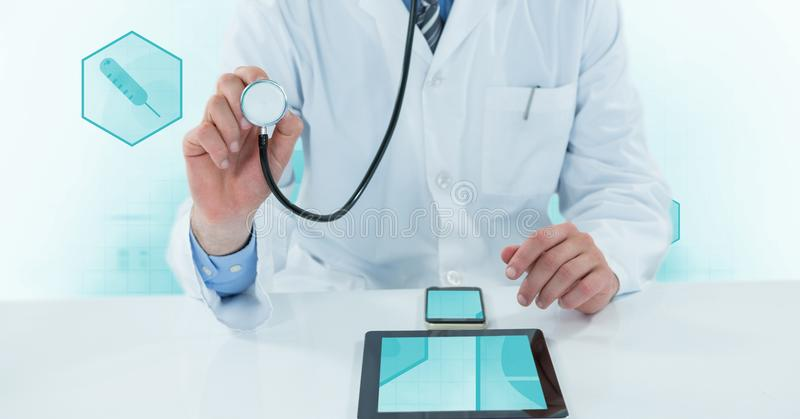 Midsection of doctor using stethoscope with digital tablet and mobile phone on desk. Digital composite of Midsection of doctor using stethoscope with digital stock photo