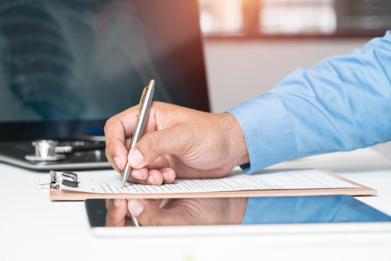 Midsection of doctor writing on paper at clinic royalty free stock photo