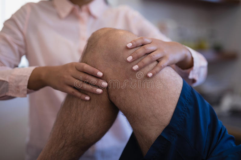 Midsection egzamininuje kolano z starszym męskim pacjentem żeński terapeuta obrazy stock