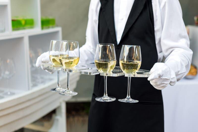 Midsection fachowy kelner w jednolitym porci winie podczas bufeta cateringu przyjęcia, świątecznego wydarzenia lub ślubu, folował zdjęcie stock