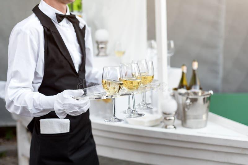 Midsection fachowy kelner w jednolitym porci winie podczas bufeta cateringu przyjęcia, świątecznego wydarzenia lub ślubu, folował zdjęcie royalty free