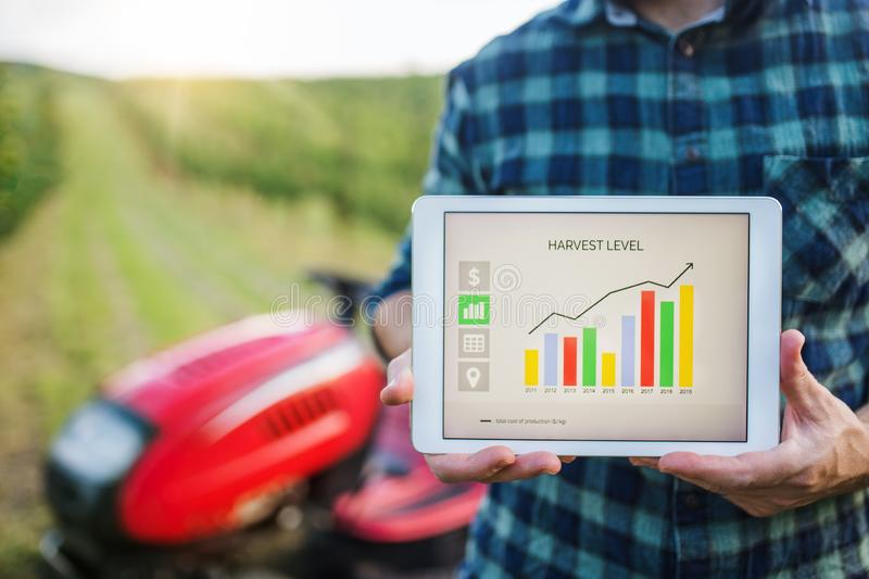 A midsection of farmer with tablet standing by mini tractor outdoors in orchard. stock images