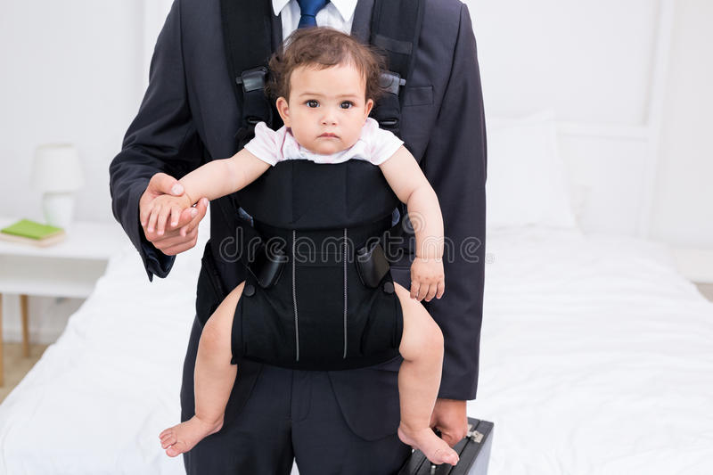 Midsection of father carrying baby and briefcase. At home stock photos