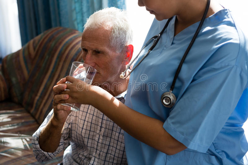 Midsection of female doctor assisting senior man in drinking water royalty free stock photo