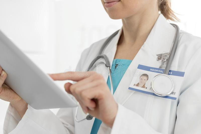 Midsection of female doctor using digital tablet at clinic stock images