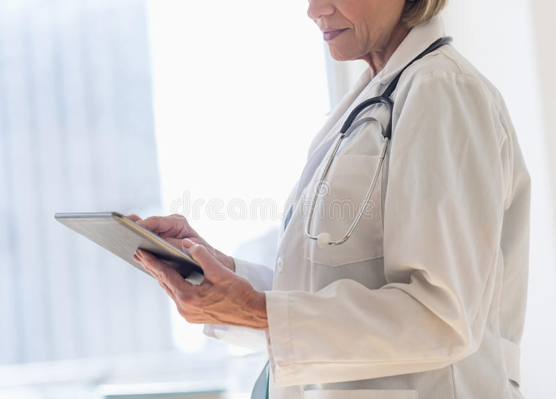 Midsection Of Female Doctor Using Digital Tablet royalty free stock photography