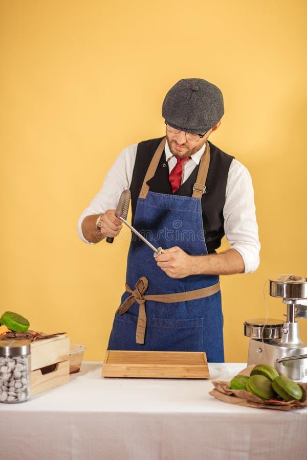 Midsection Męski szefa kuchni ostrzenia nóż W Handlowej kuchni zdjęcia stock