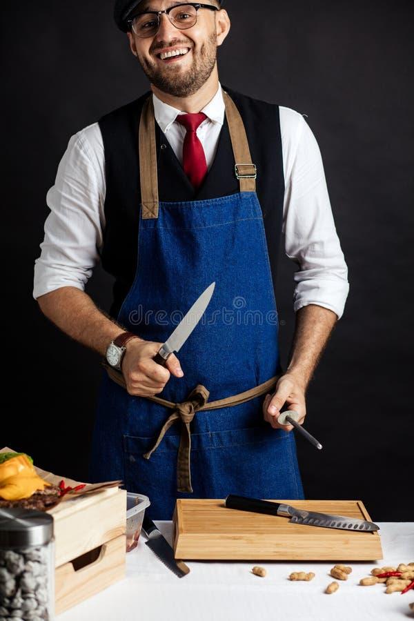 Midsection Męski szefa kuchni ostrzenia nóż W Handlowej kuchni fotografia stock