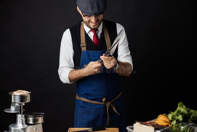 Midsection Męski szefa kuchni ostrzenia nóż W Handlowej kuchni zdjęcie stock