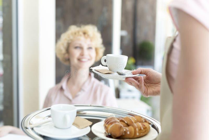 Midsection młoda kelnerki porcji kawy espresso kawa uśmiechnięty dojrzały klient przy restauracją zdjęcia royalty free