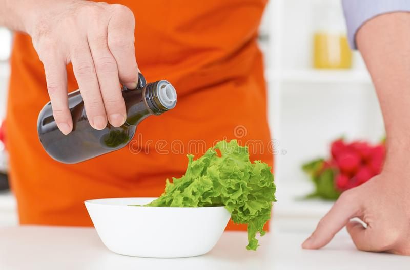 Midsection of a man pouring olive oil over fresh salad in restaurant kitchen. Concept of healthy eating royalty free stock image