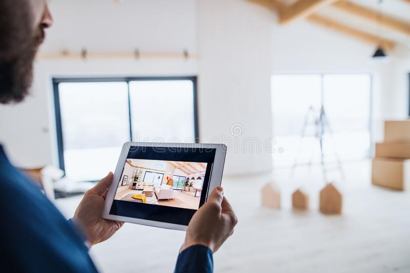 Midsection of man with tablet, looking at interior design sketches. A new home concept. royalty free stock photography