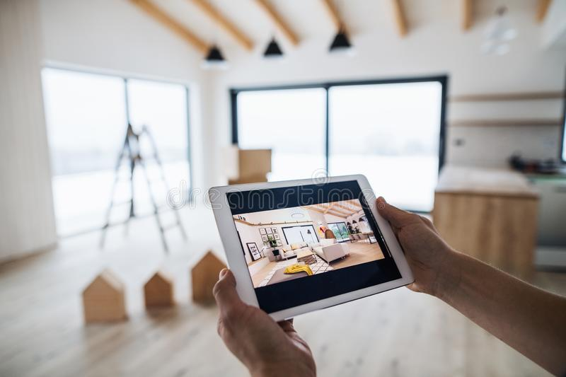 Midsection of man with tablet, looking at interior design sketches. A new home concept. A midsection of man with tablet, looking at interior design sketches. A royalty free stock photography