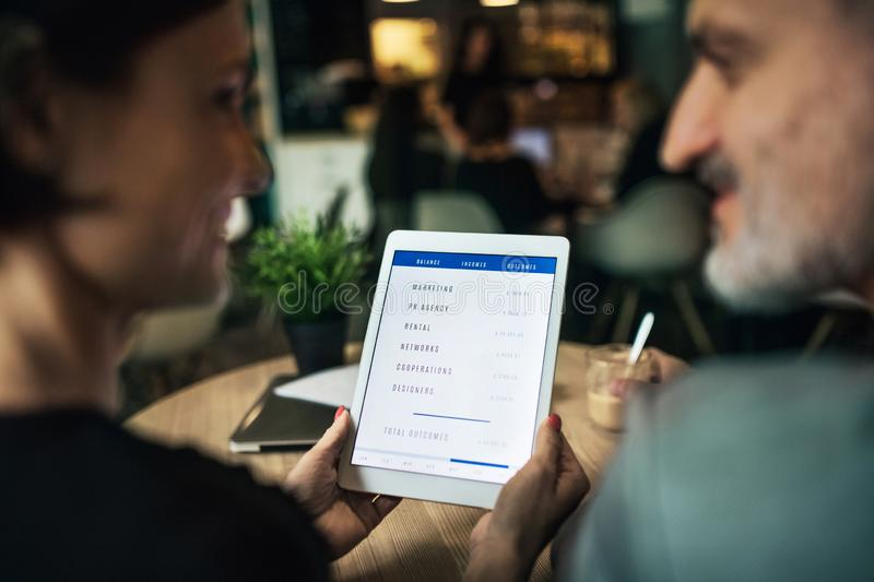 Midsection of man and woman having business meeting in a cafe, using tablet. royalty free stock photo