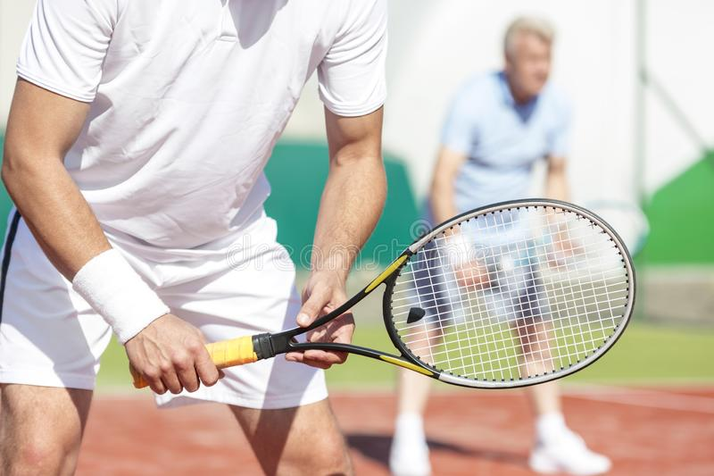 Midsection of man standing with tennis racket against friend playing doubles match on court. Midsection of men standing with tennis racket against friend playing royalty free stock image