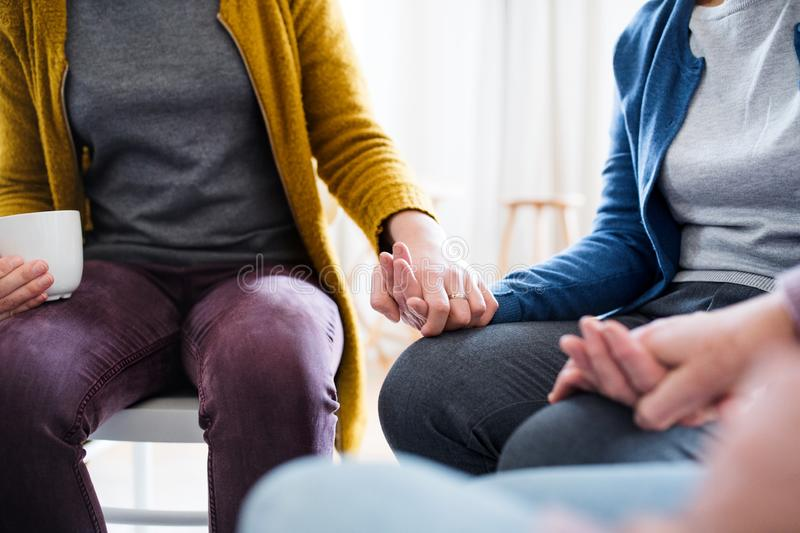 Midsection of men and women sitting in a circle during group therapy. Midsection of men and women sitting in a circle during group therapy, supporting each stock photos