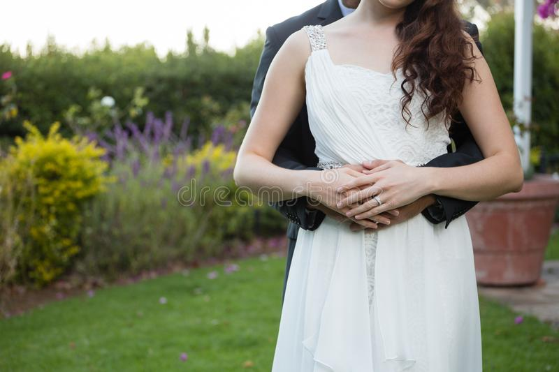 Midsection of newlywed couple embracing in park stock photography