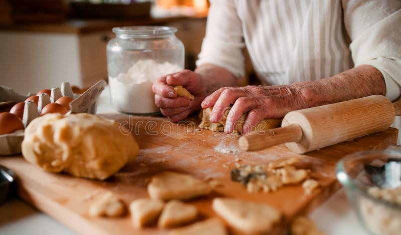 Midsection of old woman making cakes in a kitchen at home. stock photos