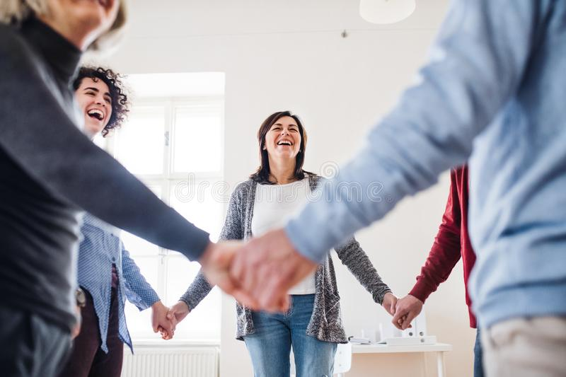 Midsection of people standing in a circle and holding hands during group therapy. royalty free stock photography