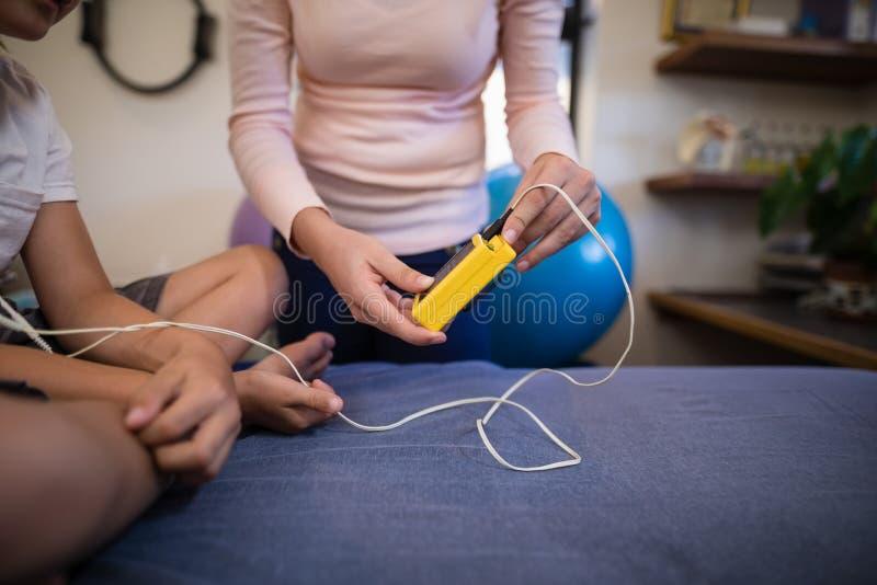 Midsection pokazuje elektryczną mięśnia pobudzenia maszynę chłopiec obsiadanie na łóżku żeński terapeuta obraz stock
