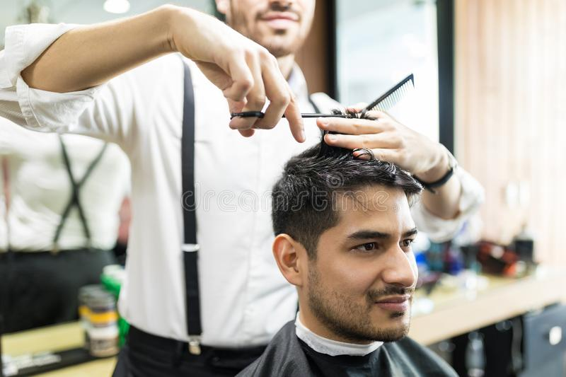 Professional Barber Giving Haircut To Male In Shop stock photos