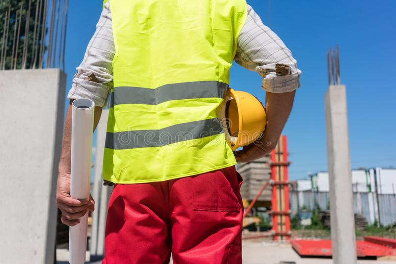 Midsection rear view of a worker holding a blueprint and a yellow hard hat royalty free stock photos